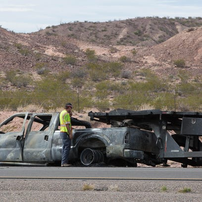 A tow truck driver starts the process of towing a burned