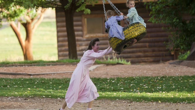An FLDS church member pushes kids on a tire swing at Cottonwood Park in Colorado City on July 6, 2011.
