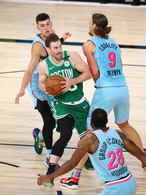 In his self-described role as a facilitator, Celtics forward Gordon Hayward, surrounded by three Miami Heat defenders, looks to pass during the game Tuesday at  the VISA Athletic Center in Lake Buena Vista, Fla.