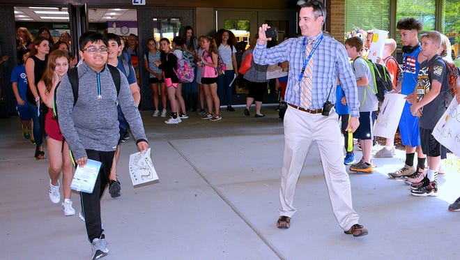 Kris Patel, left, a sixth grade student at Horseheads Intermediate School, gets a sendoff from staff and students Thursday before competing in the 2018 Scripps National Spelling Bee.