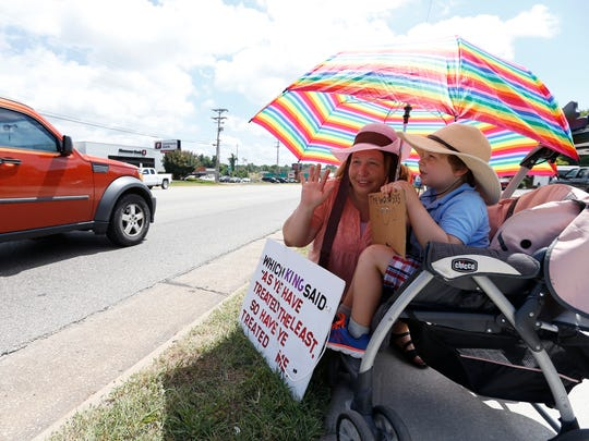 Laura and Isaiah Nickle holds signs as they protest in front of Sen. Roy Blunt's office on Wednesday afternoon to protest immigration laws that has led to a greater number of family separations along the U.S.-Mexico border.