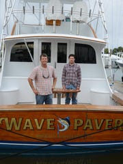 Captain Russell Sinclair and Brian Boyle stand on the deck of the Wave Paver.