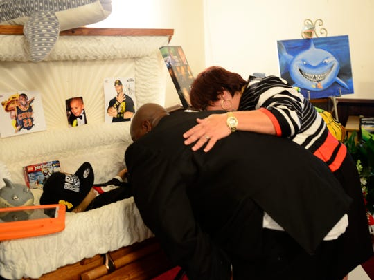 Alex Smith, left, and Brandy Lagasse say a final goodbye to Tae after his funeral service before the casket is closed.