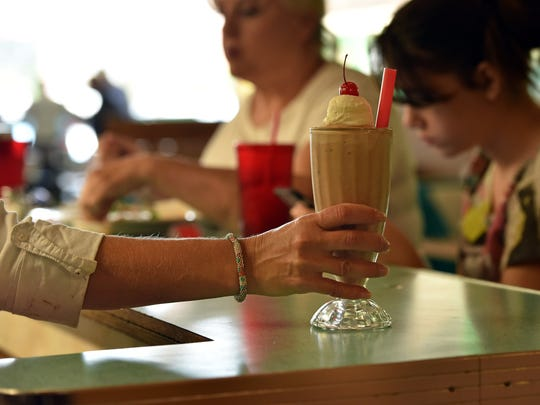 A Brent's Drugs employee serves a chocolate milkshake at the diner in Jackson's Fondren neighborhood.