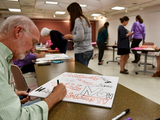 Allen Bellman, left, makes a protest sign to be used at the Women's March on Jackson at the Eudora Welty Library Tuesday. The Women's March on Jackson is scheduled for Jan. 21, from noon to 3 p.m. at the Capitol.