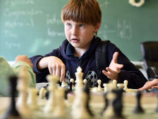 Mason Emfinger, 10, plays chess during class at the