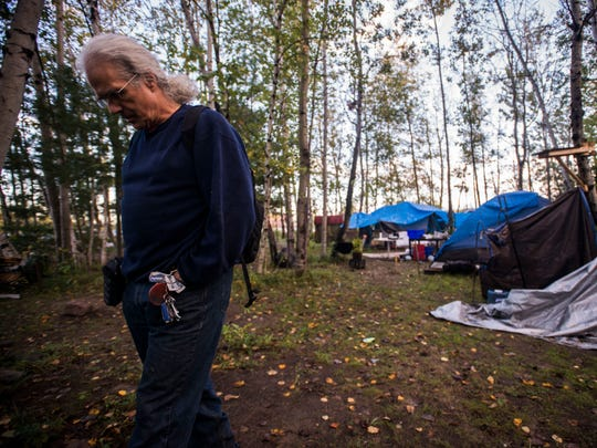 Stephen Marshall, advocate for homeless and a former resident of a camp in a patch of woods off Sears Lane in Burlington's South End, watches and waits for a warned action by the city to clear out the camp on Tuesday morning, Oct. 10, 2017. Despite plans to start work at 8 a.m. and the brief presence of a few DPW trucks, an hour later, no action had been taken.