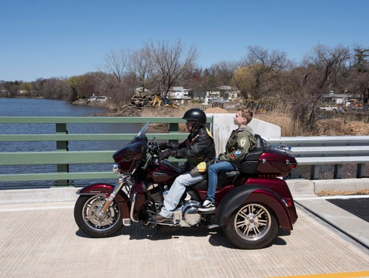 Tyler Ryan rides on the back of a three-wheeled motorcycle over the Lt. William C Ryan (USMC) Memorial Bridge during a rededication of the bridge on Saturday, April 21, 2018. Tyler Ryan is the grandson of William Ryan.