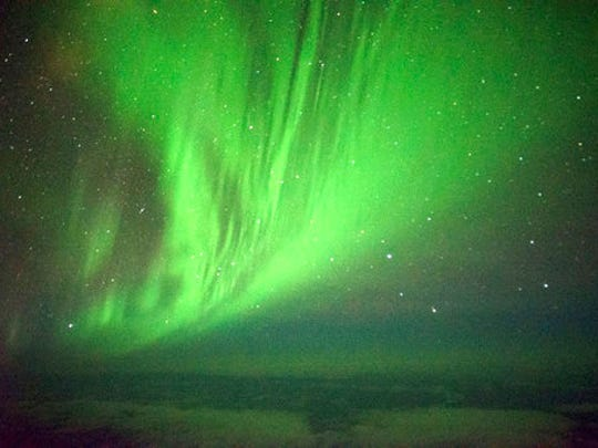 The Southern Lights are seen over the Southern Ocean near Antarctica from a chattered plane Friday, March 24, 2017. A charter plane that left Dunedin, New Zealand, late Thursday flew close to the Antarctic Circle to give the eager passengers an up-close look at the Aurora Australis, or Southern Lights.