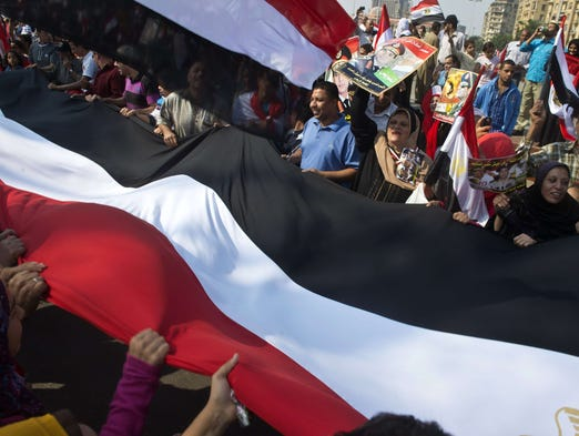 Egyptians wave a giant national flag in Tahrir Square as they mark the 40th anniversary of the 1973 Arab-Israeli War in the Egyptian capital, Cairo. Egypt braced for rival demonstrations called by supporters and opponents of deposed Islamist president Mohammed Morsi during the anniversary's festivities.