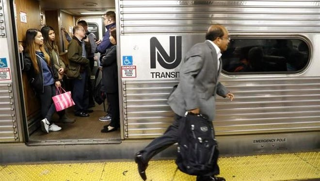 An afternoon rush-hour commuter rushes to board a crowded NJ Transit train at Penn Station on Thursday, Sept. 29, 2016.