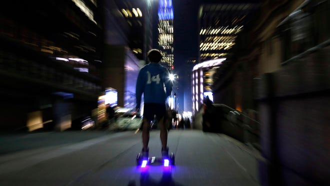A young man rides a hoverboard along a Manhattan street toward the Empire State Building in New York. More than 500,000 hoverboards are being recalled after reports that they can burst into flames.