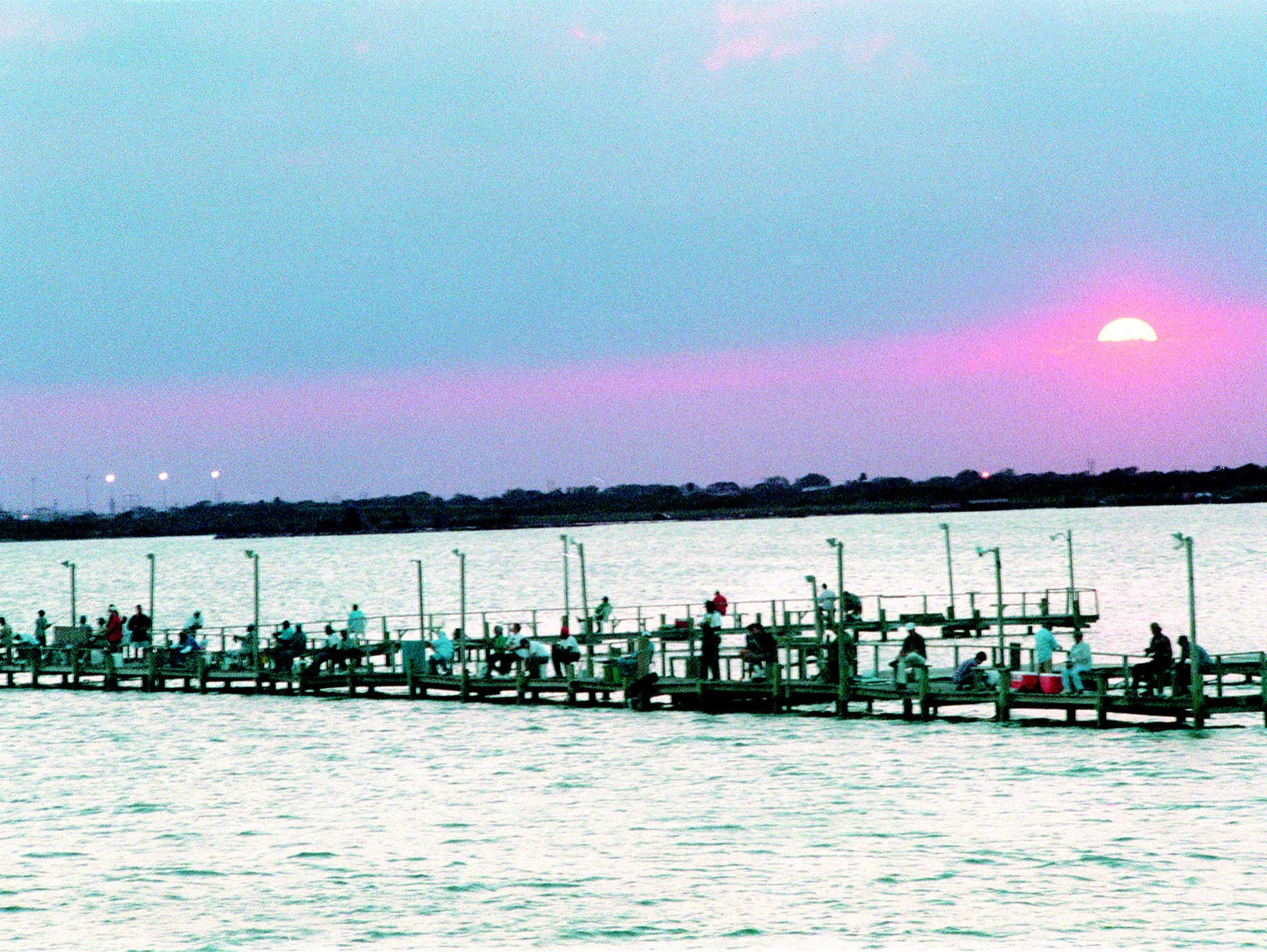 An autumn sun sets on anglers drawn to Red Dot Pier