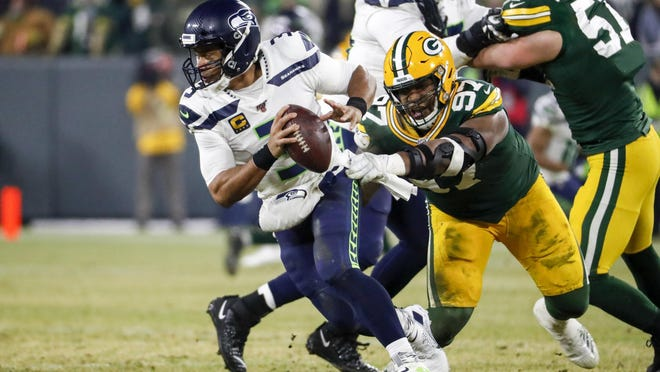 Green Bay's  Kenny Clark (97) pressures Seattle quarterback Russell Wilson during the first half of the Packers' NFL divisional home playoff win on Jan. 12.