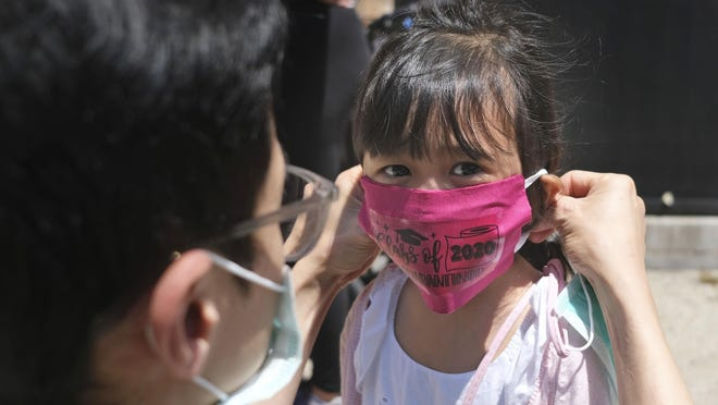 Olivia Chan's father helps her with a new mask she received during a graduation ceremony for her Pre-K class in front of Bradford School in Jersey City, N.J. on June 10. School districts across America are in the midst of wrenching decisions during the summer about how to resume classes in settings radically altered by the coronavirus pandemic, with socially distanced school buses, virtual learning, outdoor classrooms and quarantine protocols for infected children as the new norm. [Seth Wenig/The Associated Press/File)