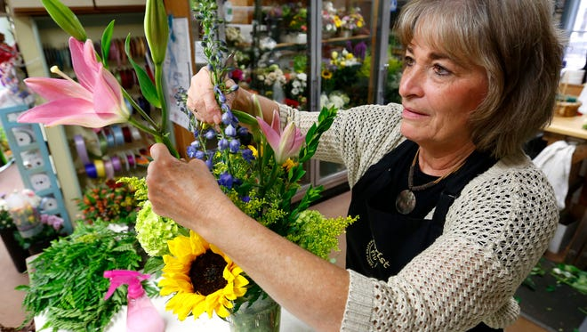 Sandy Taylor, owner of Plaza Florist & Gifts, builds a Mother's Day floral arrangement in her Urbandale shop.