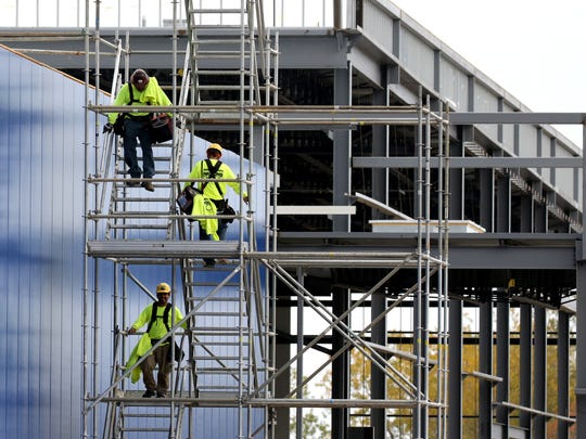 Contractors use a temporary stairwell to depart from working on the roof of the Ikea store building at West Drexel Avenue and I-94 in Oak Creek on Oct. 13.