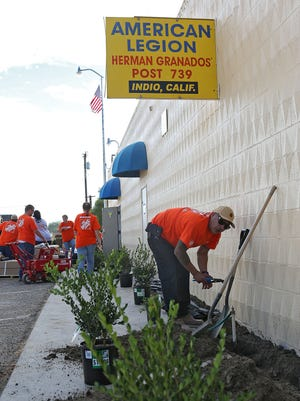 Edurardo Vega gets soil ready for new plants at the American Legion Post 739 in Indio on Wednesday. Home Depot and its employees volunteered manpower and supplies to restore the post.