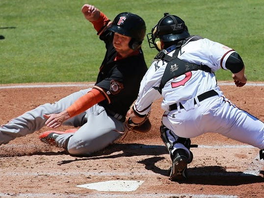 Chihuahuas' catcher Robert Kral tags out sliding Fresno baserunner Alex Presley Sunday. Presley was trying to score on a double steal.
