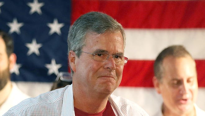 Republican presidential candidate and former Florida Governor Jeb Bush shows off a Reagan/Bush '84 tee-shirt as he speaks during a Miami field office opening on September 12, 2015 in Miami, Florida.