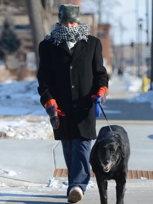 Mary Kollman and her dog, Brisco, get out for a short walk as  subzero temperatures grip the Green Bay area on Thursday morning.