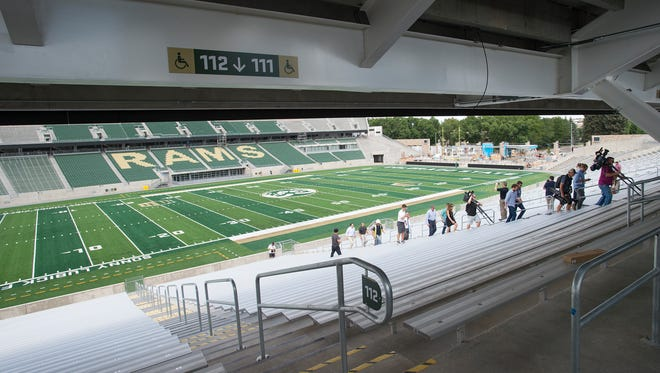 Media personnel walk up the east stands during a tour of the new CSU football stadium on Tuesday, July 18, 2017.