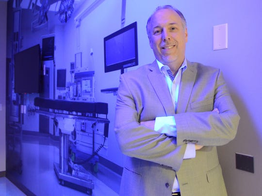 Cliff Yahnke is Clinical Affairs Director of Indigo-Clean at Kenall Manufacturing. The company makes a variety of LED lighting products at their facility at 10200 55th Street, Kenosha, Wisconsin. He was photographed Thursday April 20, 2017 in a room which shows the company's blue disinfecting LED lights against a mural photo of a hospital operating room. / Mark Hertzberg for Gannett Wisconsin Newspapers