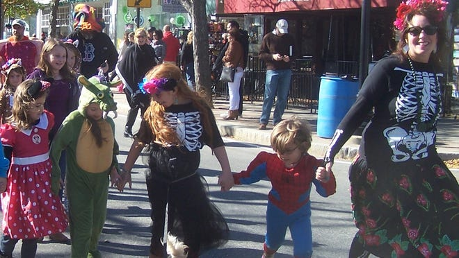 Jane Walsh, right, owner of Red Fish Blue Fish, leads the 2019 Open Streets Halloween costume parade.