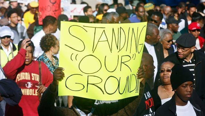 "Marchers hold up signs as they walk to the Florida Capitol on March 10, 2014, for a rally in Tallahassee. Participants were rallying against the state's ""Stand Your Ground"" laws."