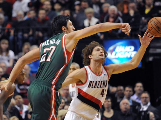 Milwaukee Bucks center Zaza Pachulia (27) knocks the ball away from Portland Trail Blazers center Robin Lopez (42) during the first half of an NBA basketball game in Portland, Ore., Tuesday, March 18, 2014. (AP Photo/Steve Dykes)