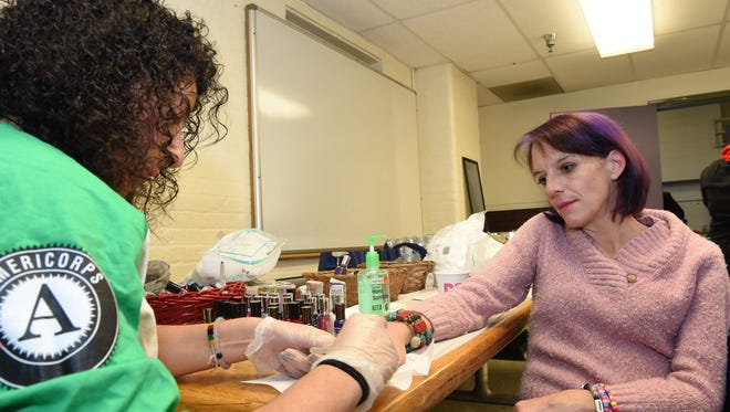 Americorps volunteer, Amy Ghattas paints Johanna Thorpe's nails during the Dutchess Project Connect held on Monday at the Family Partnership Center in the City of Poughkeepsie. Monday's event provided free haircuts, and manicures for Poughkeepsie residents in need, also available was information from other local organizations servicing the local at risk population.
