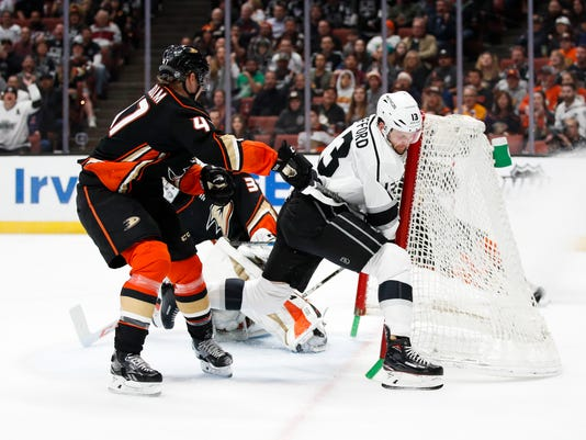 Los Angeles Kings' Kyle Clifford, left, crashes into the net after he was shoved by Anaheim Ducks' Hampus Lindholm, of Sweden, during the first period of an NHL hockey game Friday, March 30, 2018, in Anaheim, Calif. (AP Photo/Jae C. Hong)