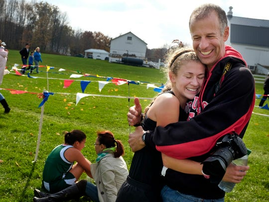 Port Huron's Rachel Bonner hugs her father, Paul Bonner, after finishing first in Division 1 of a regional cross country meet Saturday Oct. 25, 2014 at Goodells County Park.