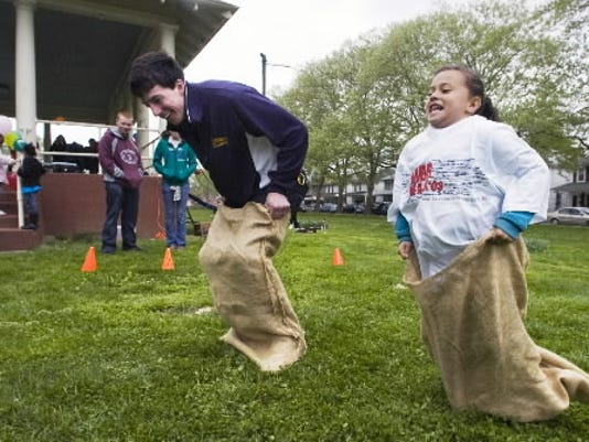 Ben McGrann, a member InterVarsity Christian Fellowship, runs a sack race with Ceyonce Burgos, age 6, during York's annual AIDS Awareness Day fair at Albemarle Park in York Sunday. YORK DAILY RECORD/SUNDAY NEWS - PAUL KUEHNEL