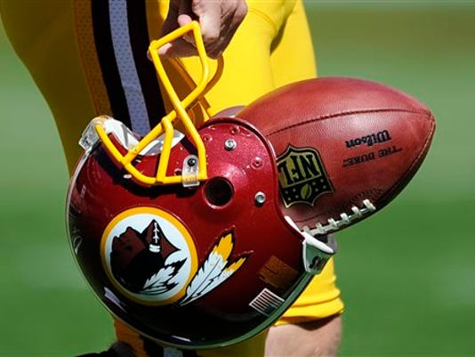 "Photo by Nick Wass - The Associated Press In this Sept. 23, 2012, file photo, Washington Redskins punter Sav Rocca carries a football in his helmet before a game against the Cincinnati Bengals. The U.S. Patent Office ruled Wednesday that the Washington Redskins nickname is ""disparaging of Native Americans"" and that the team's federal trademarks for the name must be canceled. The ruling comes after a campaign to change the name has gained momentum over the past year."