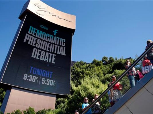 People walk under a billboard promoting the CNN Democratic presidential debate, Tuesday, Oct. 13, 2015, in Las Vegas. Democratic presidential candidates, Hillary Rodham Clinton, Jim Webb, Bernie Sanders, Lincoln Chafee, and Martin O'Malley will take the stage later today.