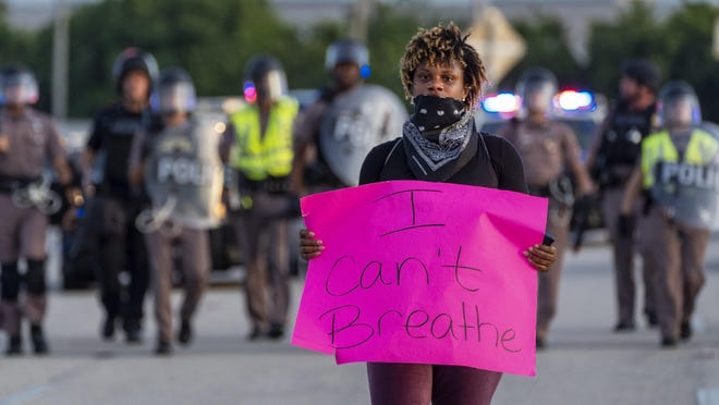 A demonstrator protesting the death of George Floyd walks down the exit ramp of Interstate 95 at Okeechobee Blvd.   on May 31, 2020, in West Palm Beach, Florida. Floyd died after being restrained by Minneapolis police officers.