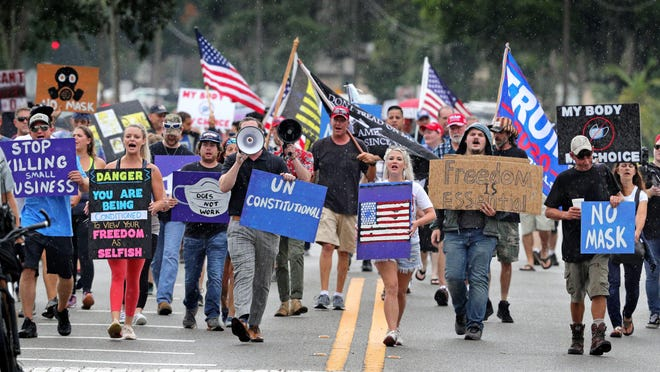 Demonstrators march through downtown Sanford, Fla., on Wednesday, July 1, to protest a Seminole county order requiring citizens to wear masks in response to the spike in coronavirus cases.