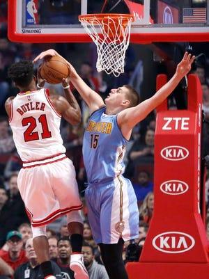 Denver Nuggets' Nikola Jokic (15) get his arm on the shot of Chicago Bulls' Jimmy Butler.