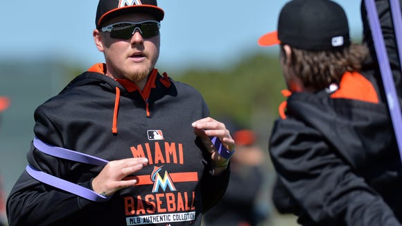 Marlins starting pitcher Mat Latos (left) talks with pitcher Jarred Cosart at Roger Dean Stadium on Feb. 20.