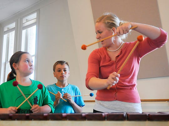 Sydney Jewell and Teddy Baumgartner take instruction from the Zimbabwe Marimba class teacher Karin Rau on Monday, Oct. 19, at the Wirth Center for the Performing Arts.