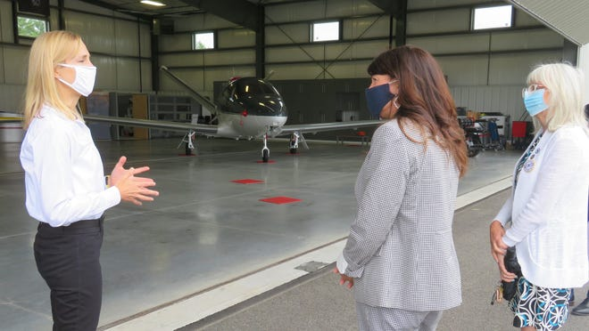 Karin Goulian, co-owner of Mike Goulian Aviation at Plymouth Airport, shows state Rep. Kathy LaNatra, D-Kingston, and state Sen. Susan Moran, D-Falmouth, around their business, with the new Cirrus Jet the Goulians use for advanced flight training in the background. [Courtesy photo]