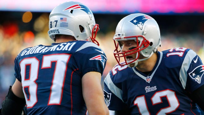 New England Patriots quarterback Tom Brady (12) celebrates with tight end Rob Gronkowski (87) after catching the ball to score a touchdown during the second half against the Miami Dolphins at Gillette Stadium.