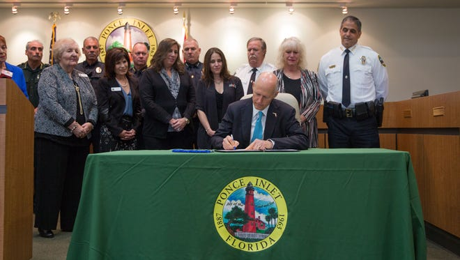 Gov. Rick Scott formally signs a law to create harsher penalties for animal abusers at a ceremony Thursday, April 5, 2018, in Ponce Inlet.