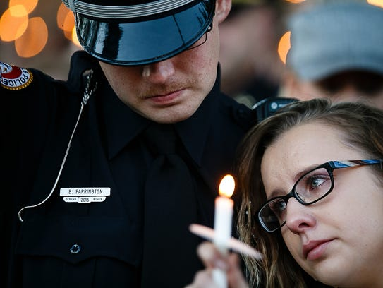 Urbandale officer Brady Farrington, left, and Megan Neal, right, raise their candles during a vigil in honor of Officer Justin Martin and Sgt. Anthony Beminio on Friday, Nov. 4, 2016 in Urbandale. Farrington and Martin were longtime friends.