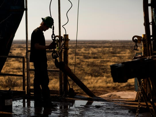 A worker waits to connect a drill bit on a Texas rig.