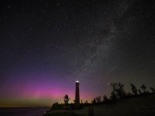 The northern lights shine over Little Sable Point Lighthouse