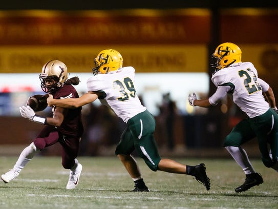 Lincoln's Vaughn Fleming rushes during their football