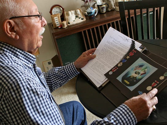 Roger Herrera looks over the military records of his
