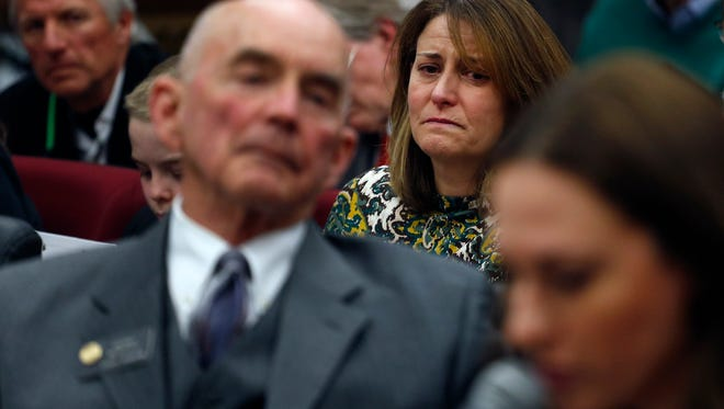 Tara Allgood, center, who lost her father the previous December to a brain tumor, cries as she listens to testimony from Melissa Brenkert, right, in favor of a bill sponsored by Colorado state senator Mike Merrifield, D-Colorado Springs, left, during a hearing of the Senate State, which would provide end-of-life options for terminally ill individuals, at the state Capitol, in Denver, Wednesday, Feb. 3, 2016.